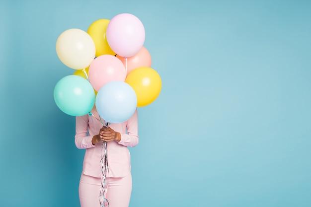 Foto de uma senhora segurando vários balões de ar coloridos escondendo o rosto