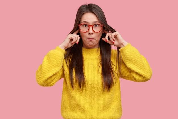 Foto de uma senhora surpresa que não suporta um som terrível, surpreendida com boatos, entope os ouvidos e usa roupas amarelas