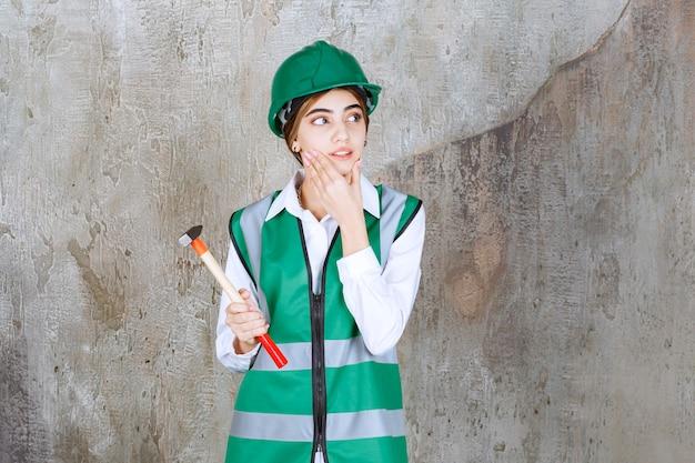 Foto de uma trabalhadora da construção civil com um capacete verde segurando um martelo