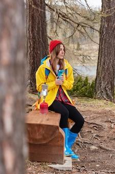 Foto de uma viajante pensativa descansando em um banco de madeira na floresta, bebendo chá da garrafa térmica, fazendo café no fogão de acampamento e usando chapéu vermelho