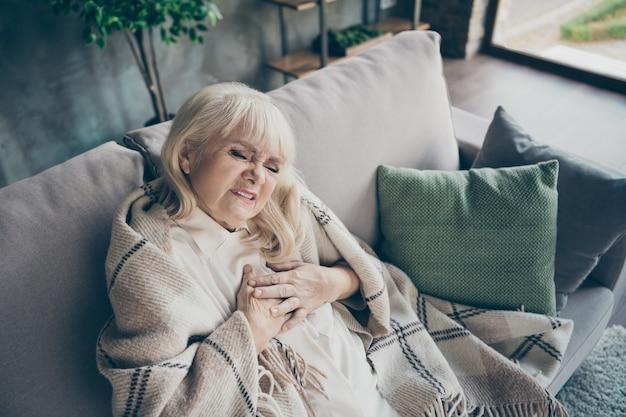 Foto de uma vovó envelhecida de cabelos brancos em desespero, segurando a zona do peito, dificuldades cardíacas, com medo de ataque cardíaco, sentado no sofá, divã coberto, manta xadrez, sala de estar