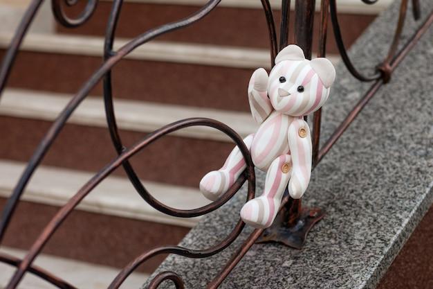 Foto de urso de brinquedo. ursinho vintage de tecido de linho. um urso de brinquedo solitário sentado na treliça forjada