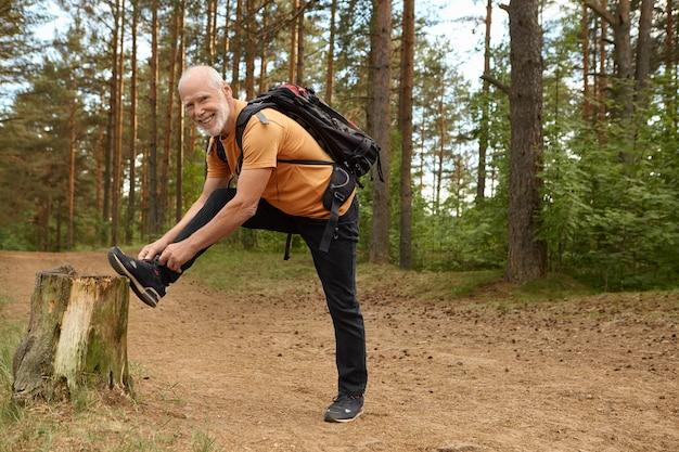 Foto de verão ao ar livre de um homem idoso saudável com mochila posando na floresta com o pé no toco, amarrando o cadarço no tênis, se preparando para uma longa escalada, caminhando com um sorriso feliz