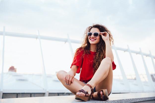 Foto de verão da garota engraçada e atraente em óculos de sol com cabelo encaracolado sentado sozinho