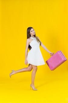 Foto de verão da linda mulher loira com mala rosa