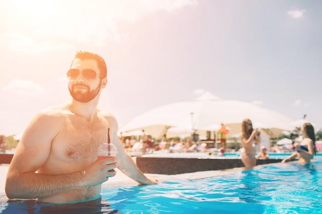 Foto de verão de um homem musculoso e sorridente na piscina