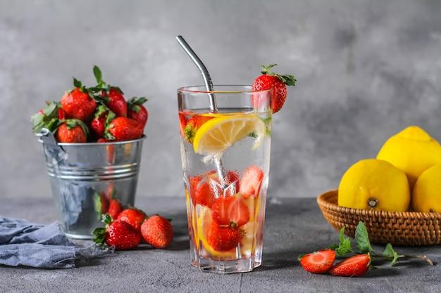 Foto de verão refrescante bebida gelada. água com infusão de morango. água mineral com limão de morangos frescos com um fundo cinza. água de desintoxicação com limão morango. copie o espaço.