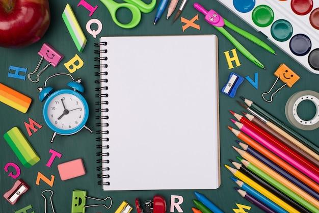 Foto de visão aérea superior de um caderno em branco com papel de carta colorido isolado em uma lousa