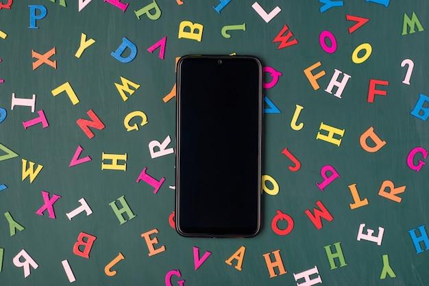 Foto de visão aérea superior de um smartphone isolado em uma lousa com letras coloridas
