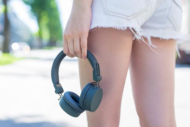 Foto de visão de baixo ângulo cortada de perto das pernas de uma senhora esportiva muito bonita e atraente em shorts jeans de brim branco, carregando fones de ouvido cinzentos da moda na mão