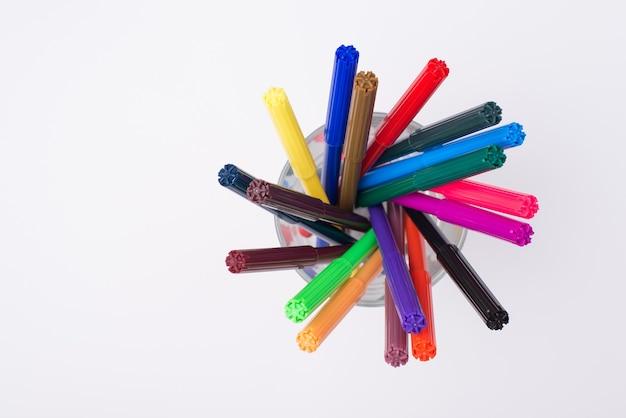 Foto de visão superior acima de marcadores coloridos em um copo de lápis isolado no fundo branco