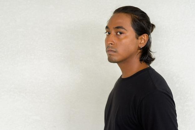 Foto de vista de perfil de um jovem indiano bonito em um fundo simples, fotografada ao ar livre com luz natural