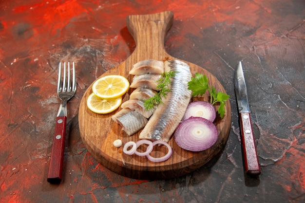 Foto de vista frontal de peixe fresco fatiado com anéis de cebola e limão em uma refeição escura de cor de carne e frutos do mar