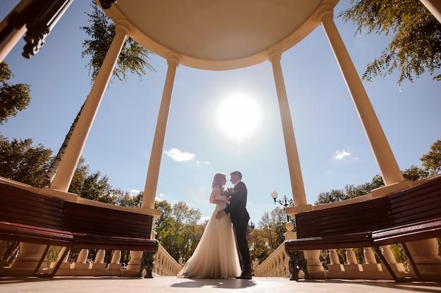 Foto de vista inferior da noiva e do noivo abraçando na rotunda