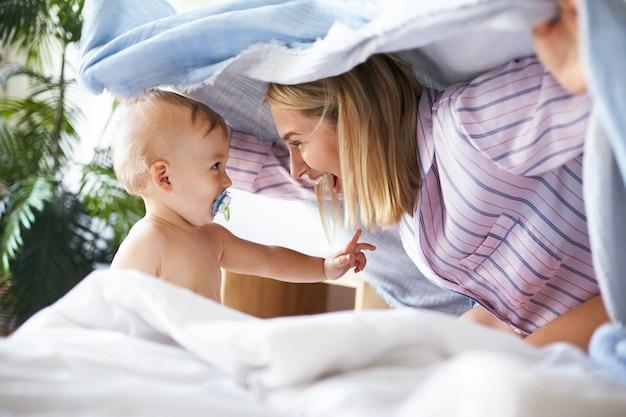 Foto de vista lateral da encantadora jovem alegre de pijama brincando de esconde-esconde com a filha da criança. criança adorável e fofa chupando chupeta, olhando para a mãe, com expressão facial divertida