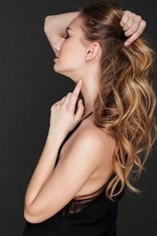 Foto de vista lateral da incrível jovem tocando o cabelo dela.