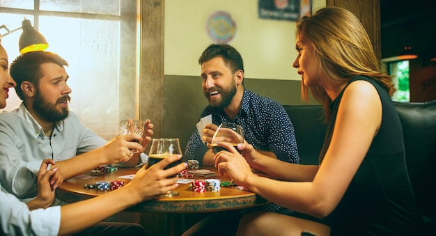 Foto de vista lateral de amigos masculinos e femininos, sentado à mesa de madeira.