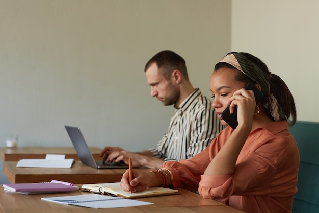 Foto de vista lateral de duas pessoas trabalhando nas mesas de um café com foco em uma jovem empresária afro-americana falando por smartphone, copie o espaço