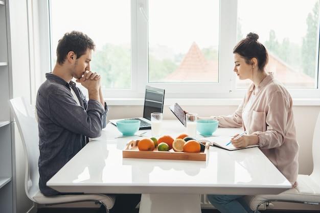 Foto de vista lateral de um casal caucasiano sentado à mesa comendo cereais com leite enquanto trabalhava no laptop