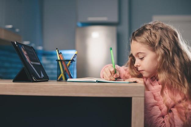 Foto de vista lateral de uma garota loira caucasiana dando aulas on-line em um tablet em casa