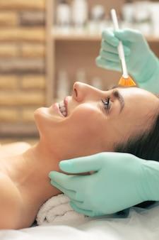 Foto de vista lateral do rosto de uma jovem sorridente expressando alegria durante o procedimento de peeling com uma escova