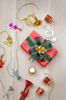 Foto de vista superior da caixa de presente embrulhada em papel vermelho pequeno com gravata borboleta de fita brilhante verde e dourada colocada na mesa de madeira com pequenos instrumentos musicais decorativos na véspera de natal ou festival de ano novo.