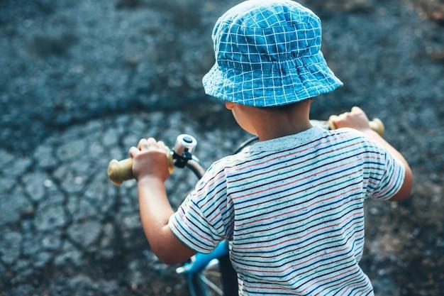 Foto de vista superior de um menino caucasiano andando de bicicleta e usando um chapéu em um dia de verão