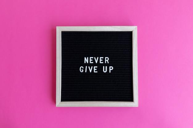 Foto de vista superior de um quadro-negro com uma massagem nunca desista em um fundo rosa