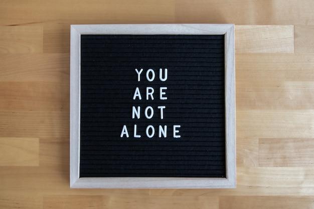 Foto de vista superior de um tabuleiro preto vazio em uma mesa de madeira com citação de você não está sozinho