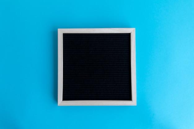 Foto de vista superior de uma lousa em branco com uma moldura de madeira em um fundo azul com espaço de cópia