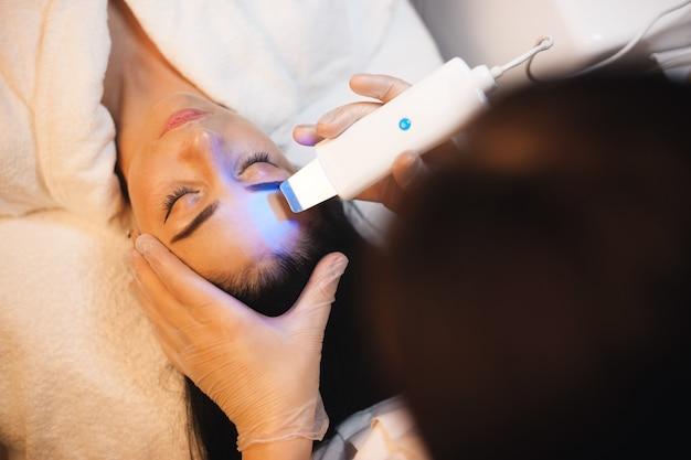 Foto de vista superior de uma mulher caucasiana passando por procedimentos de tratamento de pele facial em um salão de spa com aparelhos modernos