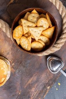 Foto de vista superior do prato marrom com biscoitos e panquecas na mesa de madeira