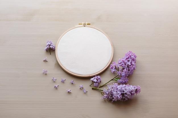 Foto de vista superior plana leiga de uma maquete com aro de bordado e flores flilac. maquete floral feminina elegante.