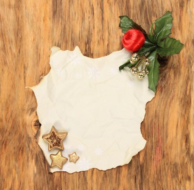Foto de vista superior vertical de um papel queimado com enfeites de natal em uma superfície de madeira