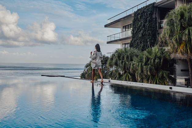 Foto de vista traseira de mulher com dreadlocks caminhando ao redor da piscina.