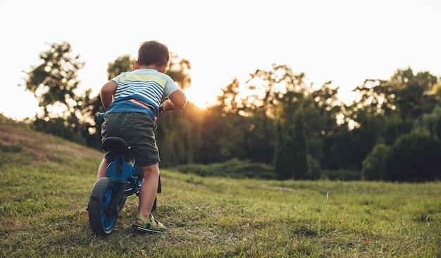 Foto de vista traseira de um menino caucasiano andando de bicicleta em um parque na grama durante um lindo pôr do sol