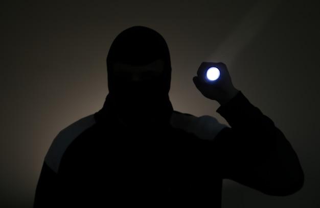 Foto desfocada. assaltante com roupas escuras segurando a lanterna. ladrão perigoso com máscara e uma tocha. homem criminoso.