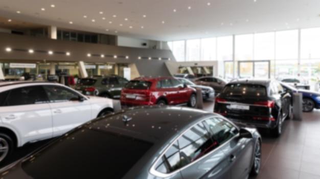 Foto desfocada de carros luxuosos no interior de uma concessionária