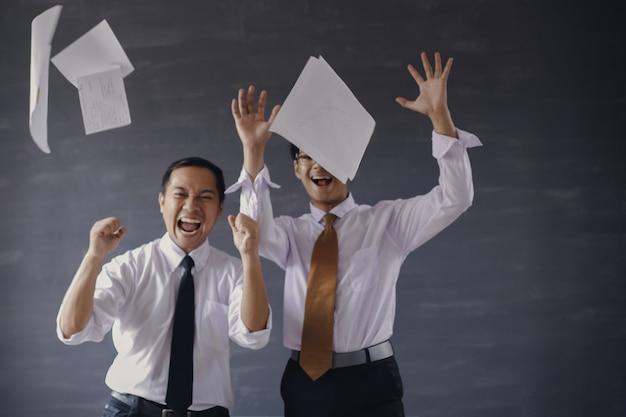 Foto desfocada de dois empresários asiáticos empolgados jogando folhas de papel