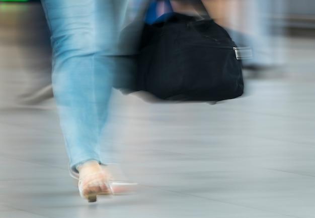 Foto desfocada de mulher com bolsa preta