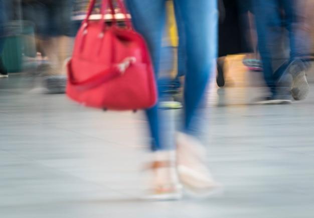 Foto desfocada de mulher com bolsa vermelha