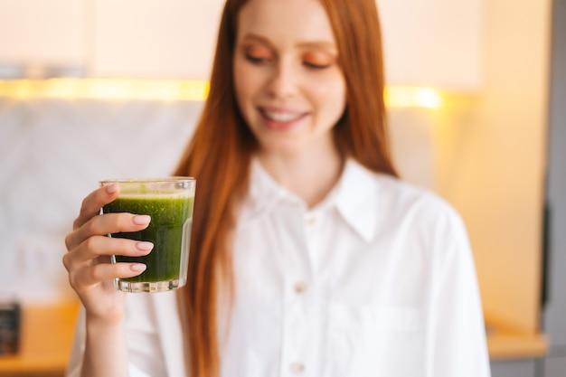 Foto desfocada de uma jovem atraente sorridente segurando um copo com desintoxicação vegetal verde