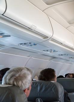 Foto desfocada do interior da aeronave. o teto do avião com compartimento de bagagem