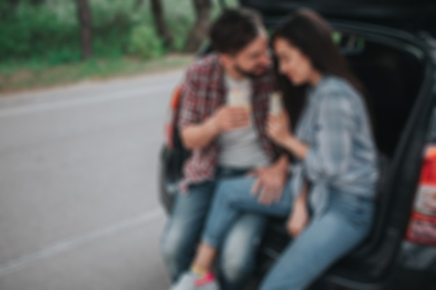 Foto desfocada do jovem casal sentado no porta-malas e segurando rolos nas mãos. cara está olhando para a garota. ela está inclinada para o ombro dele.