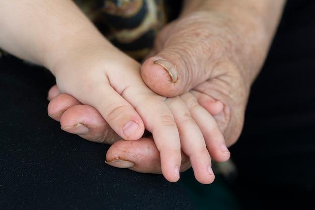 Foto detalhada da mão de um avô idoso segurando a mão de uma criança