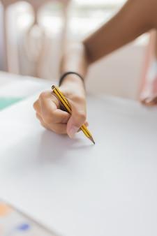 Foto detalhada sobre a mão de uma menina desenhando com lápis no papel