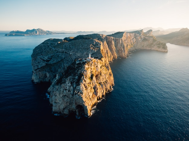Foto distante aérea de um alto penhasco rochoso com uma torre branca construída no topo no meio do oceano