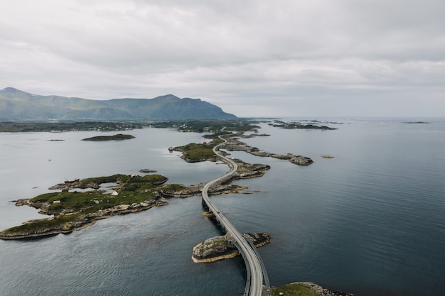Foto distante de uma longa viaduto no corpo da água cercada por pequenas ilhas