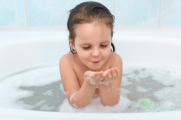 Foto do adorável bebê com cabelos molhados, brincando com espuma de sabão na banheira