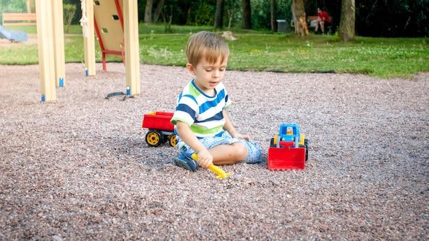Foto do adorável menino da criança de 3 anos brincando com areia e seu caminhão e reboque no parque. criança cavando e construindo em uma caixa de areia